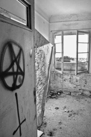 Satanic symbols graffiti on the door of an abandoned house. Black and white. Stock Photo - 9316245