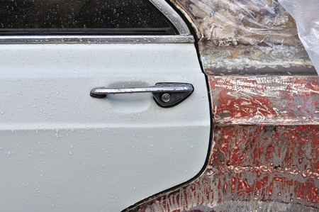 scraped: Vintage car window and scraped metal door with raindrops. Background texture. Stock Photo