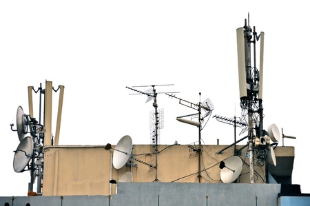 Telecommunication antenna and satellite dish receivers on building rooftop. Isolated on white background.