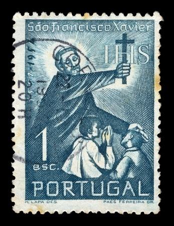 PORTUGAL - CIRCA 1952. Vintage canceled postage stamp with illustration of Saint Francis Xavier holding a cross and blessing two children, circa 1952. Stock Illustration - 9428801