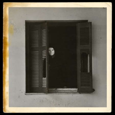 urban decline: Vintage photograph of masked figure by the broken windows of abandoned house. Stock Photo