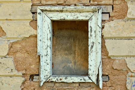 Empty wooden window frame and chipped wall texture. Grunge background.