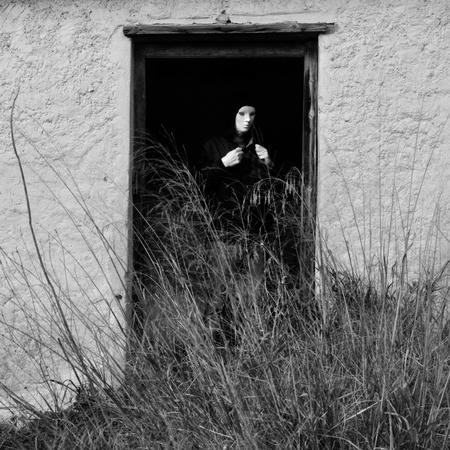pervert: Masked figure by broken door of abandoned house obscured by overgrown plants.