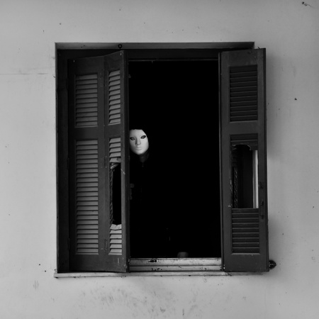 Masked figure by the broken windows of an abandoned house. photo