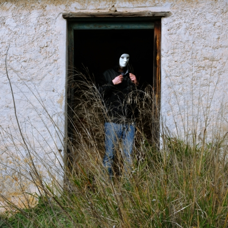Man with white mask by broken door of abandoned house and overgrown plants.