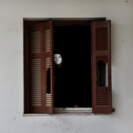 pervert: Man with white mask by the broken window shutter of an abandoned house. Stock Photo