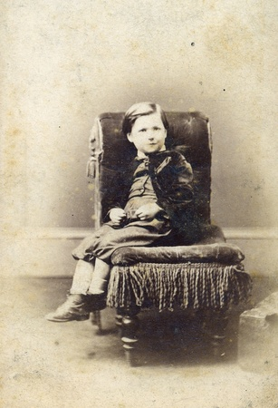 Portrait of Victorian young boy on chair  Sourced from antique cabinet card vintage photograph created by A D  Lewis, Newcastle on Tyne, UK, circa 1870