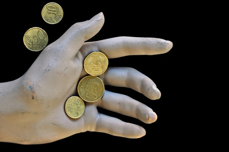 financial issues: Worn doll hand holding euro coins  Economic and financial issues  Stock Photo