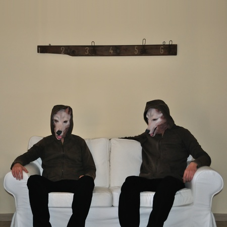 Two human figures with dog animal mask sitting on sofa couch.
