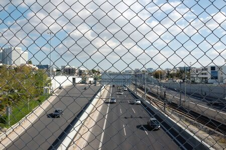 chain link fence: Cars on the motorway and chain link fence. City traffic. Stock Photo