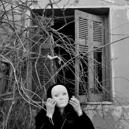 atrocity: Figure with white mask under window with overgrown plants and doll hand. Black and white.