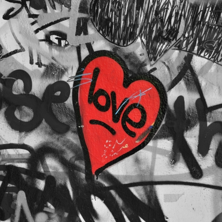 modern love: Red painted love heart on graffiti covered black and white wall background  Selective saturation