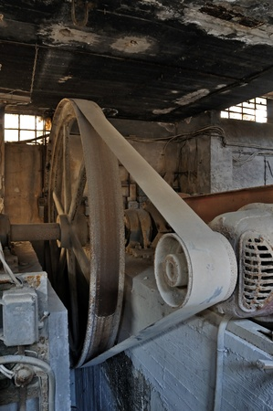 Rusty wheel belt driven machinery in abandoned factory. Industrial interior.