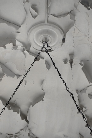 deteriorating: Rusty chains and chipped paint white ceiling texture in abandoned interior. Stock Photo
