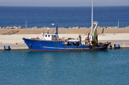 Fishing trawler in port. Rusty dragger ship tied to shore. Stock Photo - 13898304