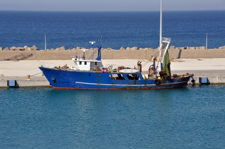 Fishing trawler in port. Rusty dragger ship tied to shore. photo