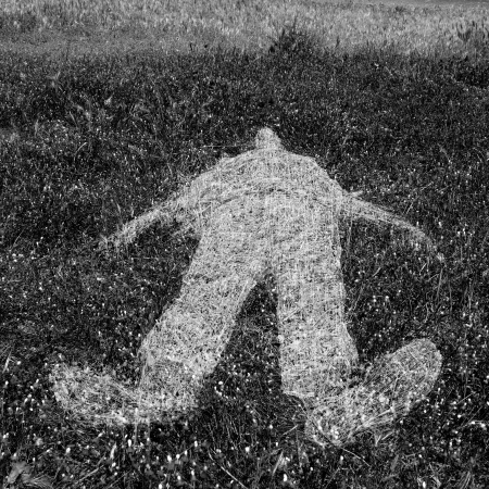 body outline: Reclining human figure outline imprinted on grass. Black and white.