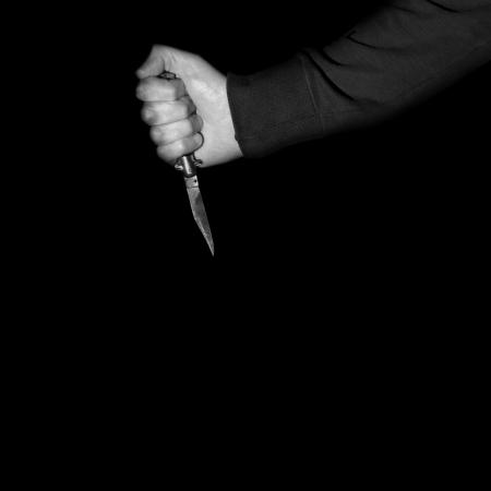 Killer holding vintage folding knive stiletto switchblade. Violent crime social issues.