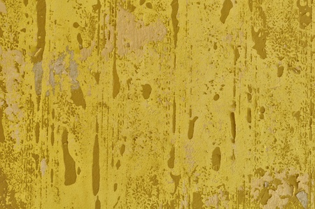 deteriorating: Peeling paint yellow wall and pieces of torn wallpaper. Background texture.