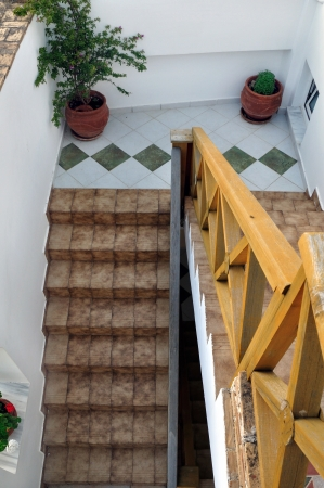 Wooden banister and tiled stairway with plant tubs. Architectural detail. photo