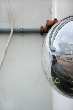 hemispherical: View of cityscape reflected on convex parking mirror. Abstract background.