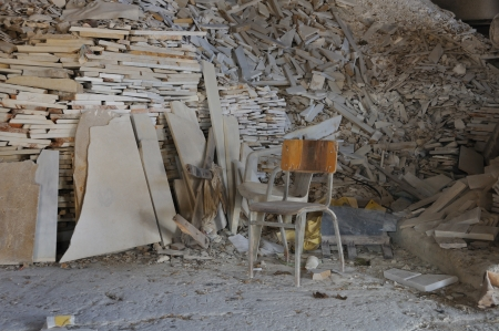 ramshackle: Dusty chair and pile of broken marble in abandoned factory interior.