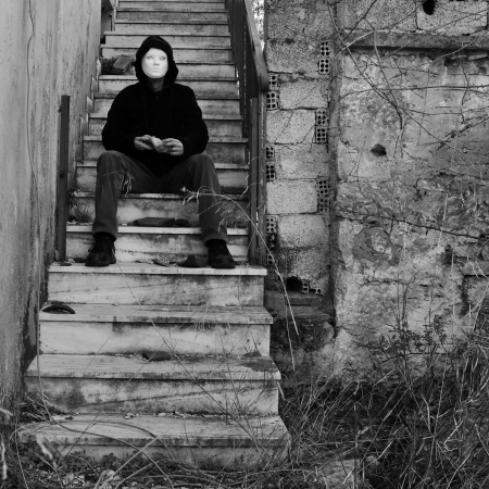 broken house: Masked figure with doll hand sitting on abandoned house staircase. Black and white. Stock Photo