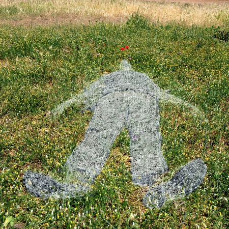 Withered grass ghostlike human figure imprint on green field. photo