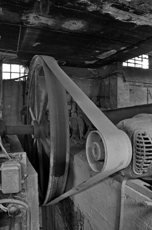 Rusty wheel belt driven machinery in abandoned factory interior. Black and white. photo