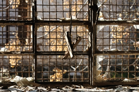 crumbling: Broken glass window and rusty wire mesh background in abandoned warehouse.