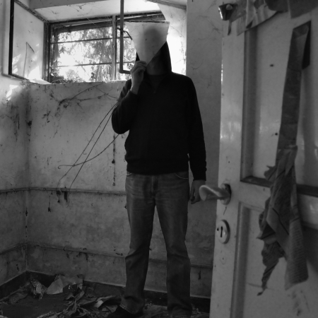 obscured: Hooded man obscured by piece of broken glass in decayed dirty room.