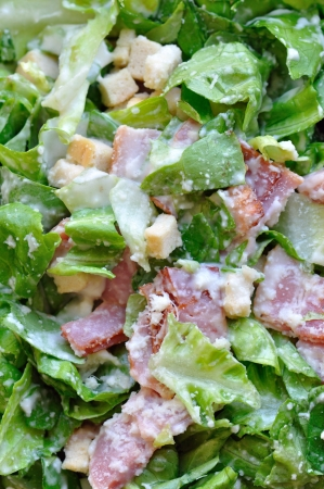 ensalada cesar: Caesar ensalada con lechuga, bacon y picatostes. Comida fondo.