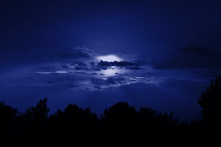 obscured: Full moon obscured by clouds. Night sky moonlight nature background.