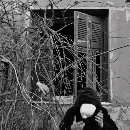 Masked figure in black and overgrown dead plants. Black and white, motion blur. photo