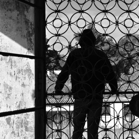 Man on the balcony of an abandoned house, metal door pattern. Black and white. photo