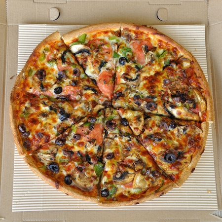 Pizza with pepperoni, mushrooms, pepper, and olives. Italian fast food background. photo
