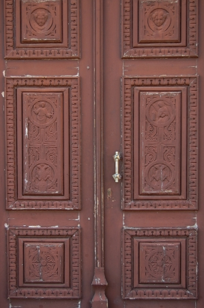 Wooden church door with carved religious symbols. Angels and cross motif. photo