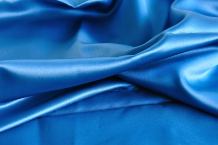 rippled: Blue fabric texture. Folded silk textile abstract background.