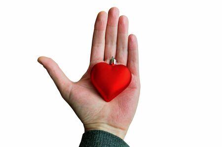 bondad: Mano que sostiene la chuchería corazón rojo. Amor de la Navidad de fondo concepto de temporada.