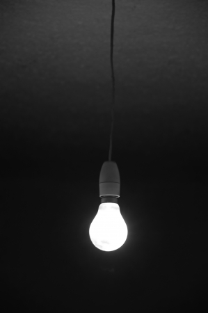 Incandescent bare light bulb glowing in dark room. Abstract background.