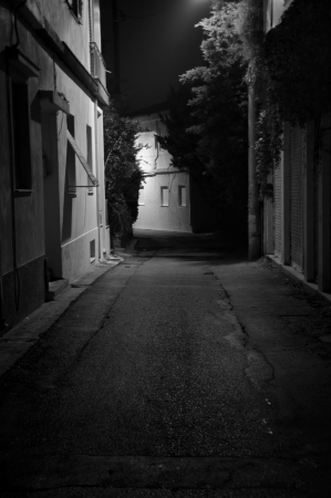 Dark alley and houses city backstreet at night. Black and white.