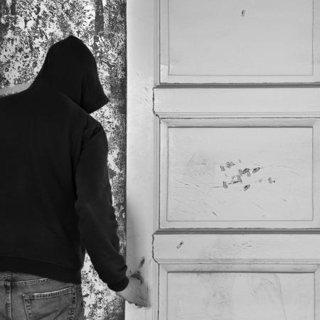 abriendo puerta: Figura encapuchada salir por la puerta de una casa abandonada. Foto de archivo