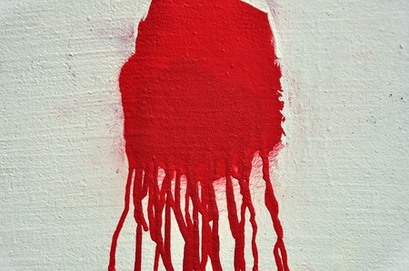gunshot: Red paint drips over textured white wall. Abstract background.