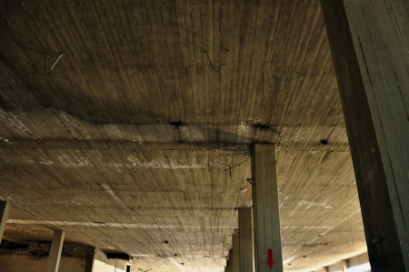 urban decline: Concrete ceiling and pillars in abandoned factory interior. Industrial architecture.