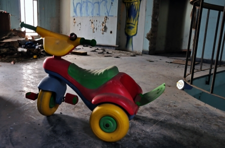 Little kids tricycle toy bike in abandoned house decayed interior. Social issues. photo