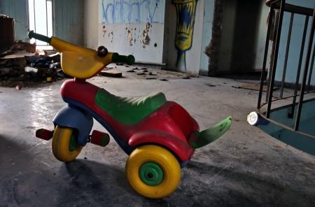 dientes sucios: Los niños pequeños bicicleta triciclo de juguete en casa abandonada decayó interior. Las cuestiones sociales.