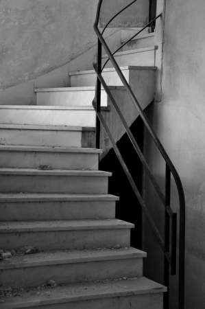 absence: Dirty marble staircase in abandoned interior. Architectural detail, black and white.
