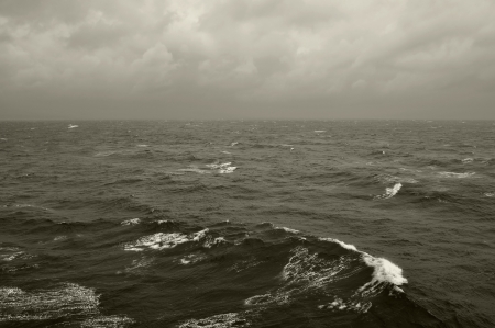 Winter sea waves and cloudy sky horizon. Black and white. photo