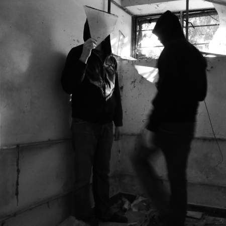 urban decline: Man holding glass fragment and blurry figure with sunlight reflected from broken window. Black and white.
