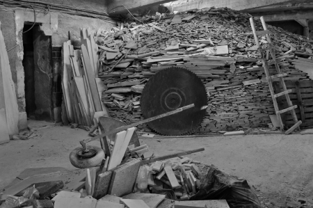 old mining building: Pile of marble scrap and rusty industrial cutting wheel in abandoned factory interior. Black and white. Stock Photo